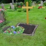 Urnenloch ausgeschmückt, Grabanlage in Erde, Holzkreuz