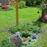 Urnenloch ausgeschmückt, Grabanlage mit Tanne abgedeckt, Holzkreuz